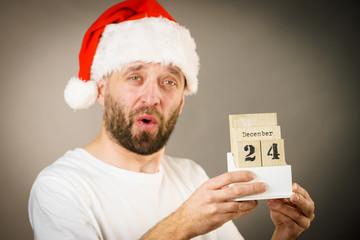 December 24th. Man santa hat holds calender