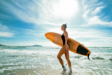 Beautiful sexy and sporty girl surfer walks with a board on the beach. Active lifestyle and recreation in Vietnam.