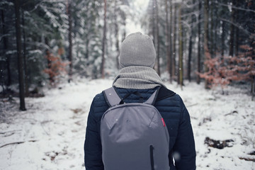 Winter tourism. Male traveler with a backpack in the winter forest. Winter trip. Man on a winter forest road