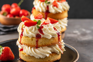 Victoria sponge cake with strawberries, jam and whipped cream on dark background. Copy space.