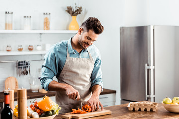 smiling young man in apron cutting fresh pepper in kitchen - fototapety na wymiar