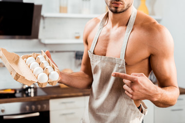 cropped shot of sexy bare-chested man in apron pointing with finger at egg carton - fototapety na wymiar