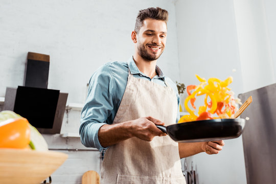 low angle view of smiling young man in apron holding frying pan with vegetables
