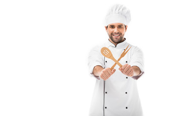 smiling young chef holding wooden kitchen utensils and looking at camera isolated on white
