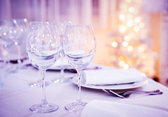 Beautiful Christmas table set. Wine glasses on celebration party