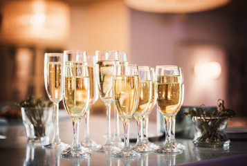 Champagne wine into wine glasses. Champagne flutes on a wedding reception or on celebration party