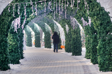 Arches of fir branches in a Christmas winter park, people walk. Selective Focus.