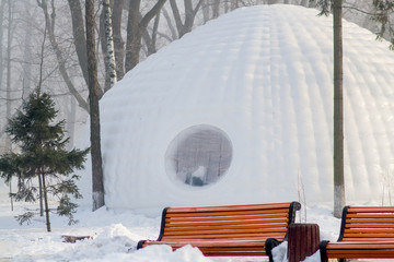 Snow igloo house in the winter park. Park decorated to Christmas winter holidays. Selective focus