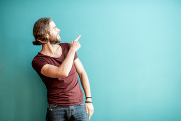 Portrait of a young caucasian bearded man with long hair dressed in t-shirt showing with hand on the colorful background