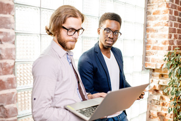 Two young businessmen dressed casually standing together with laptop near the brick wall with glass...