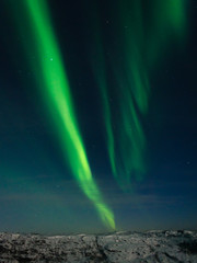 Beautiful stripes of the northern lights, aurora in the night sky above the hills.