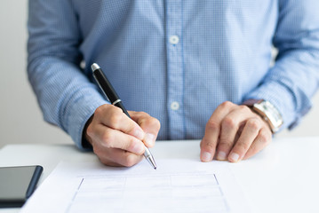 Closeup of candidate signing application form. Business person sitting at desk. Recruitment concept. Cropped front view.