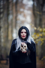 Picture of witch woman in black cloak with skull