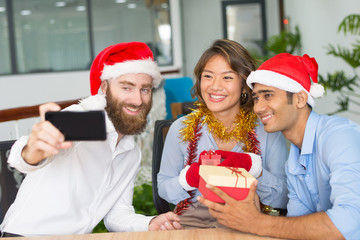 Cheerful business team taking Christmas selfie. Multiethnic group of colleagues in Santa hats and mittens holding gifts and having fun at office. Christmas selfie concept