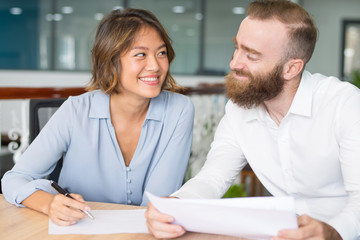 Cheerful office employees flirting and joking while working on papers. Two business colleagues smiling at each other while working on papers. Office dating or paperwork concept