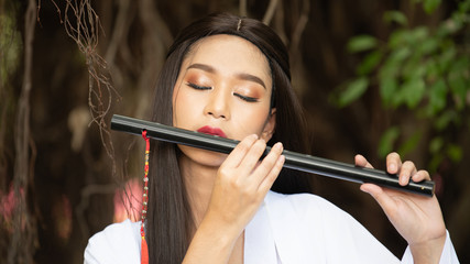 Chinese girl is playing the traditional Chinese musical instrument; Asia young woman play flute in the nature.