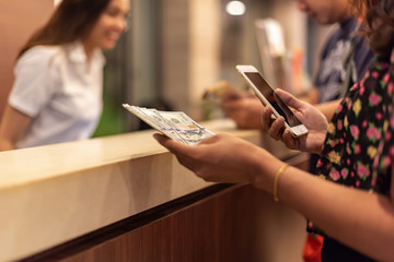 young woman holding money and using mobile smartphone with button online booking flight or hotel, easy life, modern lifestyle,online marketing concept.