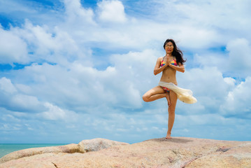 The woman with yoga posture on the beach at sunset; gorgeous young woman practicing yoga outdoor.