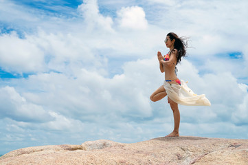 The woman with yoga posture on the beach; gorgeous young woman practicing yoga outdoor.