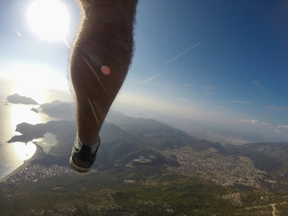 blue sky and man's leg doing paragliding