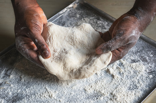 Man holding dough in the kitchen