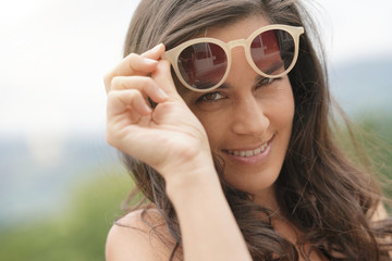 Portrait of smiling brunette woman wearing sunglasses