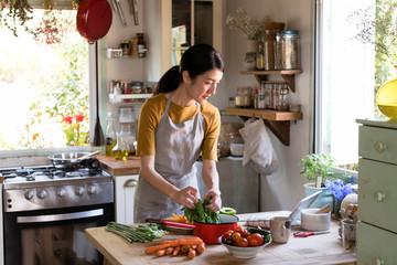 Aziatische vrouw bezig met koken in de keuken