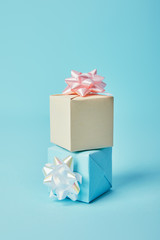 Gift boxes with white and pink bows on blue background