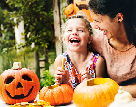 Young cheerful girl carving pumpkins with her mom