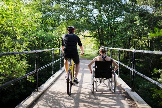 Couple on a exercising together on a bicycle and in a wheelchair