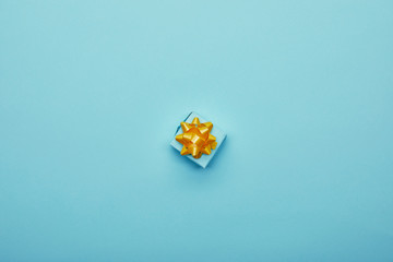 Top view of bright gift box with golden bow on blue background