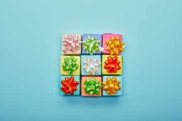Top view of colorful gifts with bows on blue background