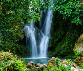 View to tall cascade falling to pond in green forest in long exposure