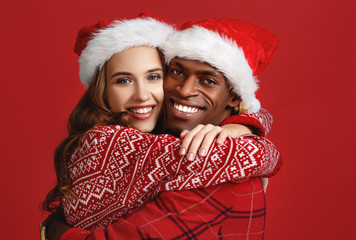 happy couple black man and caucasian woman in christmas hats on red background