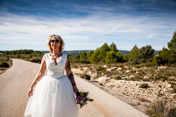 Bride with bouquet walks along a lonely road in a rural landscape