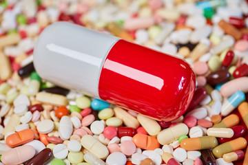 Große Pille und viele bunte Medikamente