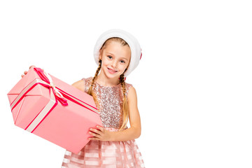 adorable little child in santa hat holding gift box and looking at camera isolated on white