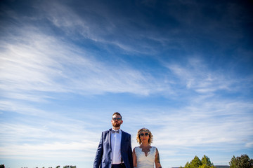 Couple of newlyweds pose together under a blue sky