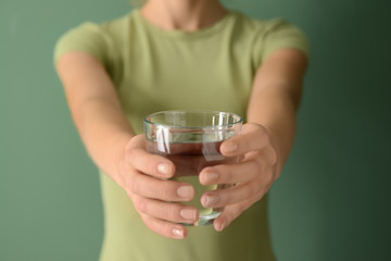 Woman holding glass of fresh water on color background