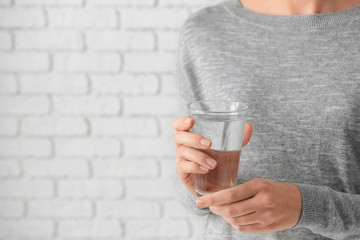 Woman holding glass of fresh water on light background, closeup