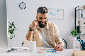 Male designer sitting and looking at color palette in office