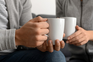 Young couple with cups of tea, closeup