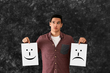 Young man holding sheets of paper with drawn emoticons on grey background