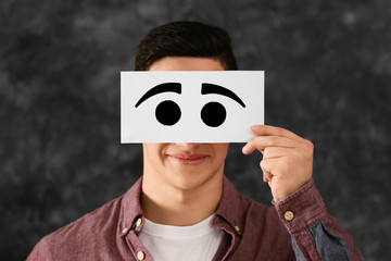 Emotional young man hiding face behind sheet of paper with drawn eyes on grey background
