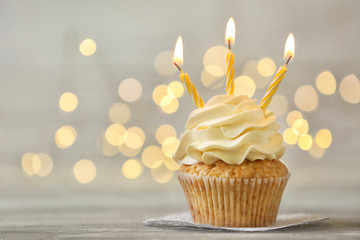 Delicious birthday cupcake with burning candles on grey table  against blurred lights