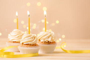 Delicious birthday cupcakes with burning candles on wooden table  against blurred lights