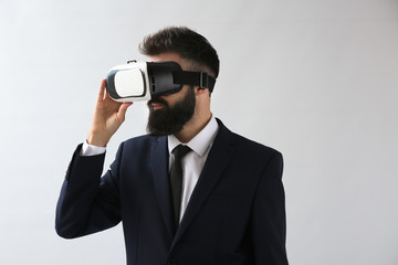 Businessman wearing virtual reality glasses on light background
