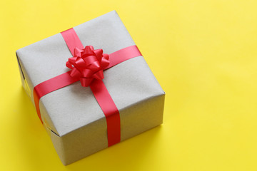 Brown Christmas gift box placed on a yellow art paper floor and have copy space.