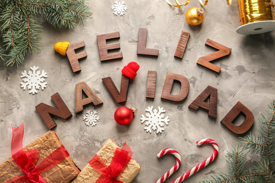 Words FELIZ NAVIDAD made with wooden letters and Christmas decorations on grey background