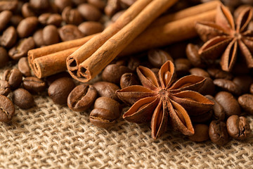 Coffee beans, anise and cinnamon on brown burlap. Close up